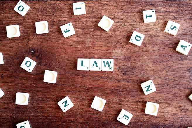 scrabble steine auf einer braunen holzfläche drei davon bilden das wort law