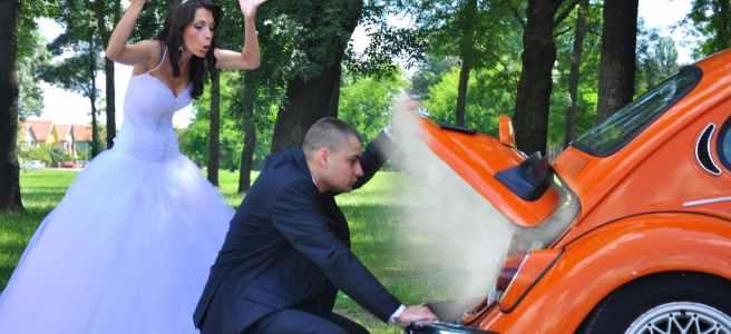 Brautleute hinter einem orangen auto mit einem schaden