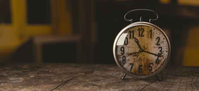 Eine alte Uhr auf einem alten Holztisch - es ist 17 nach elf