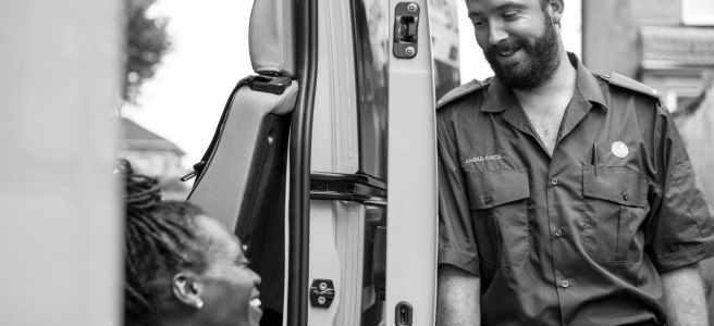 eine in einem Rettungswagen sitzende Sanitäterin spricht mit einem danebenstehenden Sanitäter
