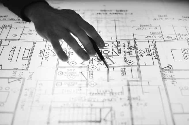 Eine Persone zeigt mit der Rechten Hand und einem Stift etwas auf einem Plan