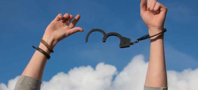 Jemand haltet die Arme zum Himmel. An einem Arm befindet sich eine Handschelle, die auf der anderen Seite offen ist.