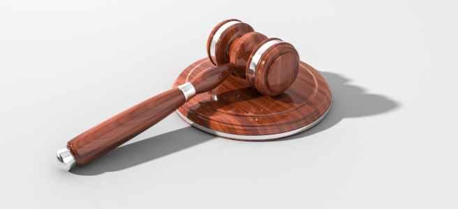 Der Hammer eines Richters liegt auf einer braunen Scheibe
