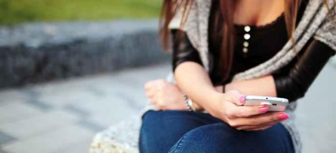 Eine Frau die auf einem Stein sitzt und in ihr Smartphone schaut