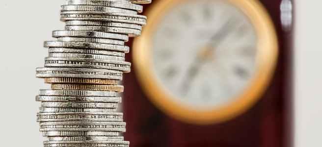 Silber- und Goldmünzen vor einer Uhr die an der Wand hängt