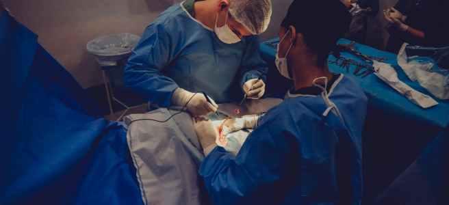 Man sieht Ärzte die einen Patienten operieren. Den Patienten selbst kann man aber nicht direkt sehen, sondern nur einen Ausschnitt der Wunde.